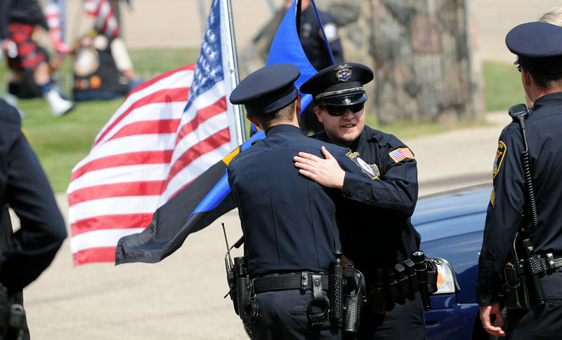 . Police officers greet each other as they enter Acacia Park Cemetery for the burial of officer Scott Patrick Wednesday.  (Pioneer Press: Jean Pieri)