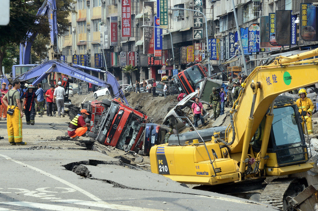 . Rescue workers search through the explosion site in southern Kaohsiung city on August 1, 2014.  A series of powerful gas blasts killed at least 22 people and injured up to 270 in the southern Taiwanese city of Kaohsiung, overturning cars and ripping open roads, officials said.   AFP PHOTO / SAM YEH/AFP/Getty Images