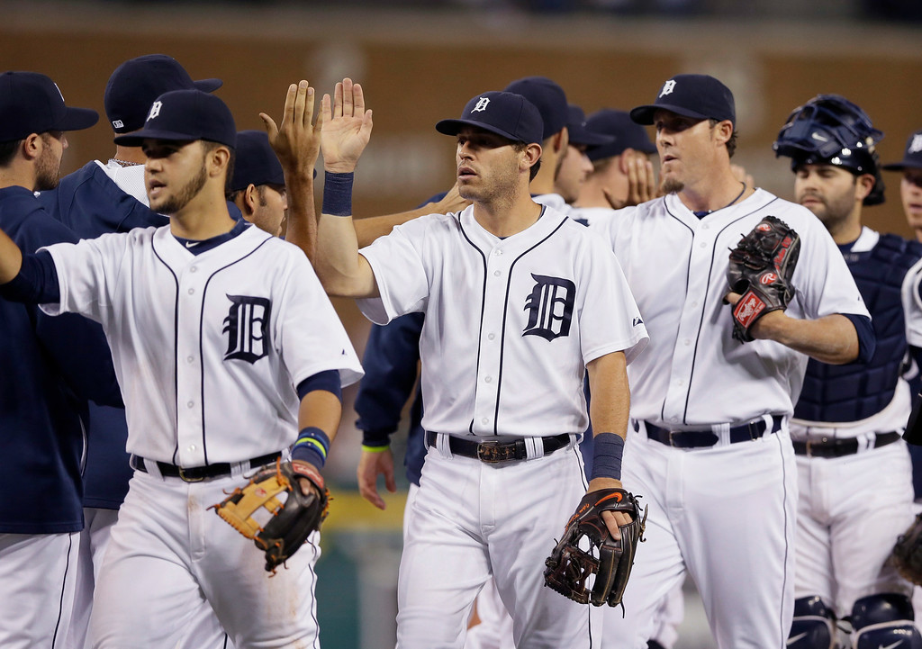 . From left, Detroit Tigers shortstop Eugenio Suarez, second baseman Ian Kinsler, relief pitcher Joe Nathan and catcher Alex Avila greet teammates after their 8-4 win over the Pittsburgh Pirates in an interleague baseball game, Wednesday, Aug. 13, 2014 in Detroit. (AP Photo/Carlos Osorio)
