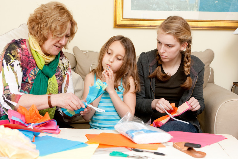 Abi teaches Arayana and Claudia how to make paper flowers.