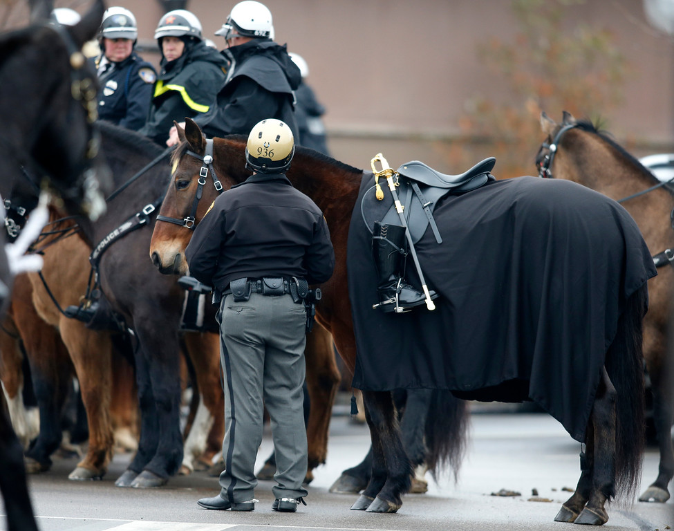 . A riderless horse is seen outside of St. Paul the Apostle Catholic Church before funeral services for Westerville police officers Anthony Morelli and Eric Joering at in Westerville, Ohio, Friday, Feb. 16, 2018. The two veteran officers were shot after entering a residence Saturday. The officers returned fire, wounding 30-year-old Quentin Smith, who has been charged with aggravated murder and remains hospitalized. (AP Photo/Paul Vernon)