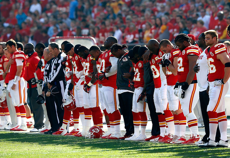 . The Kansas City Chiefs pause for a moment of silence honoring domestic abuse after the incident involving Jovan Belcher #59 prior to the game at Arrowhead Stadium on December 2, 2012 in Kansas City, Missouri.  (Photo by Jamie Squire/Getty Images)