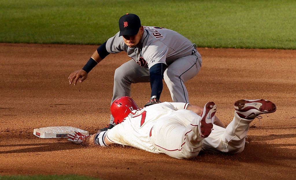 . St. Louis Cardinals\' Matt Holliday, bottom, is tagged out by Detroit Tigers shortstop Jose Iglesias while trying to stretch a single into a double during the 10th inning of a baseball game Saturday, May 16, 2015, in St. Louis. The Tigers won 4-3 in 10 innings. (AP Photo/Jeff Roberson)
