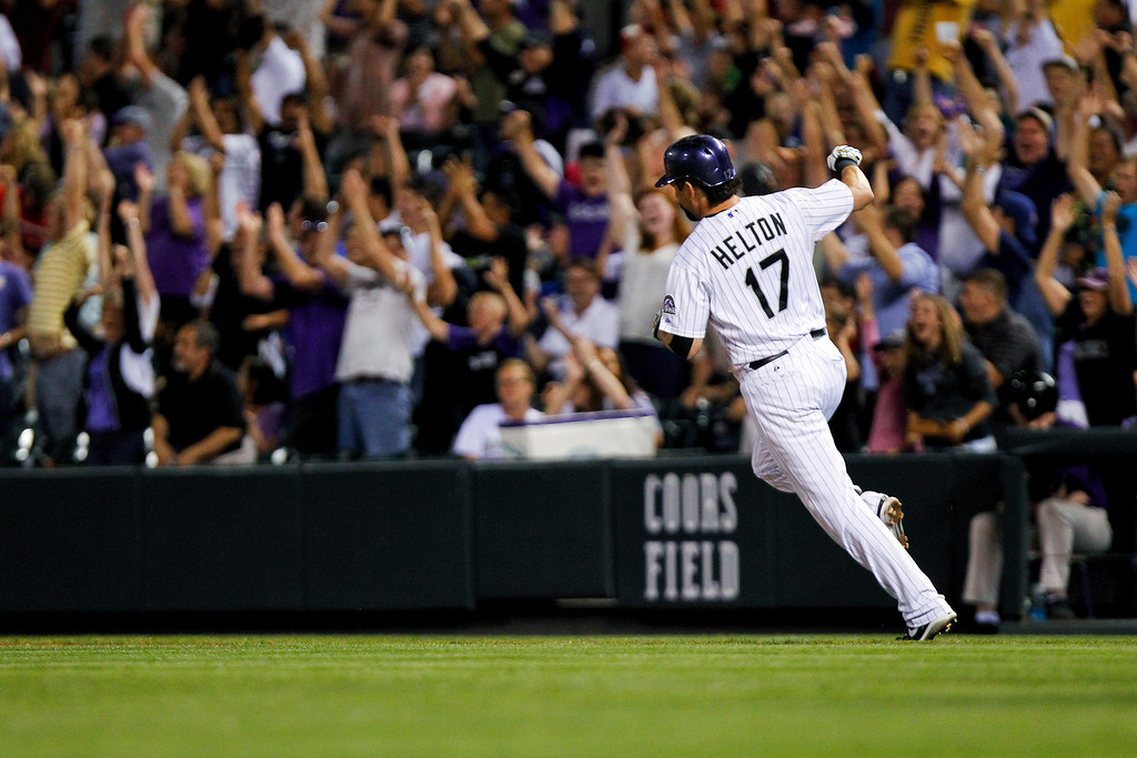 . Colorado Rockies\' Todd Helton raises his fist after hitting a three-run home run on a pitch by Cincinnati Reds\' Logan Ondrusek during the seventh inning of a baseball game, Friday, Aug. 30, 2013, in Denver. (AP Photo/Barry Gutierrez)