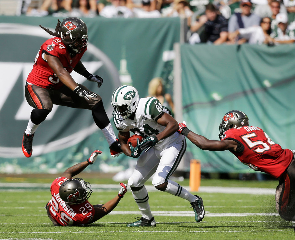 . New York Jets wide receiver Stephen Hill (84) runs with the ball as Tampa Bay Buccaneers defensive end Adrian Clayborn (94), cornerback Leonard Johnson (29) and outside linebacker Lavonte David (54) defend during the second half of an NFL football game, Sunday, Sept. 8, 2013, in East Rutherford, N.J. (AP Photo/Mel Evans)