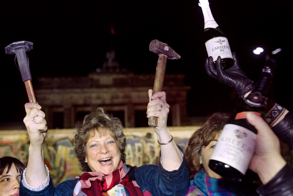 . A berliner holds up a hammer and a chisel early on November 15, 1989 in front of the wall at the Brandebourg Gate partly visible behind it as a crowd of people demonstrated for the destruction of the wall for a passage way between the East and the West near the monument.       (Photo credit GERARD MALIE/AFP/Getty Images)