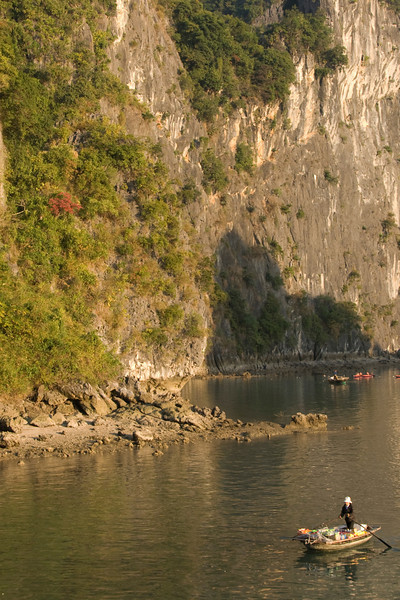 Solitary boat against steep rock cliffs - Ha Long Bay, Vietnam