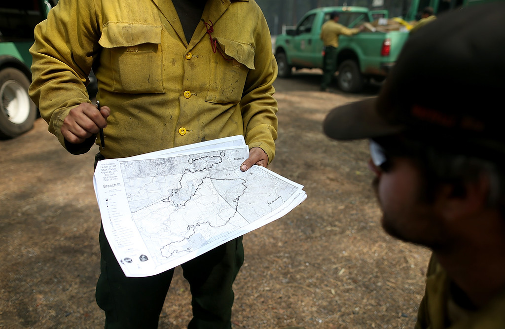 . U.S. Forest Service firefighters look at an incident map as they take a break from battling the Rim Fire at Camp Mather on August 25, 2013 near Groveland, California.  (Photo by Justin Sullivan/Getty Images)