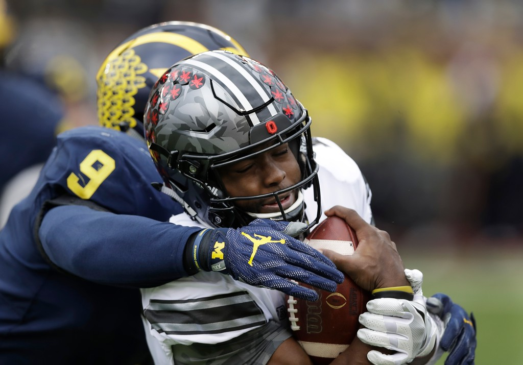 . Ohio State quarterback J.T. Barrett (16) is sacked by Michigan linebacker Mike McCray (9) during the first half of an NCAA college football game, Saturday, Nov. 25, 2017, in Ann Arbor, Mich. (AP Photo/Carlos Osorio)