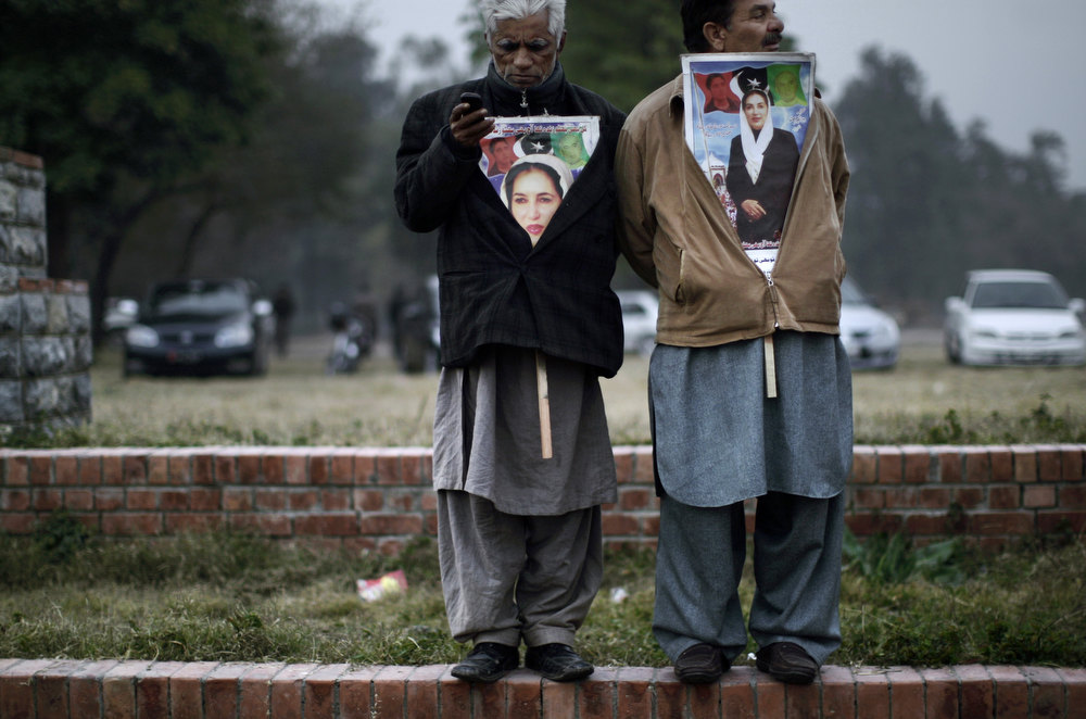 Description of . Supporters of Pakistan's slain leader Benazir Bhutto, one listens to speeches, right,  and the other checks his mobile phone, at a ceremony to mark the fifth anniversary of her death, in Islamabad, Pakistan, Thursday, Dec. 27, 2012. The 24-year-old son of former Pakistani Prime Minister Benazir Bhutto has launched his political career with a fiery speech on the fifth anniversary of his mother's assassination. (AP Photo/Muhammed Muheisen)