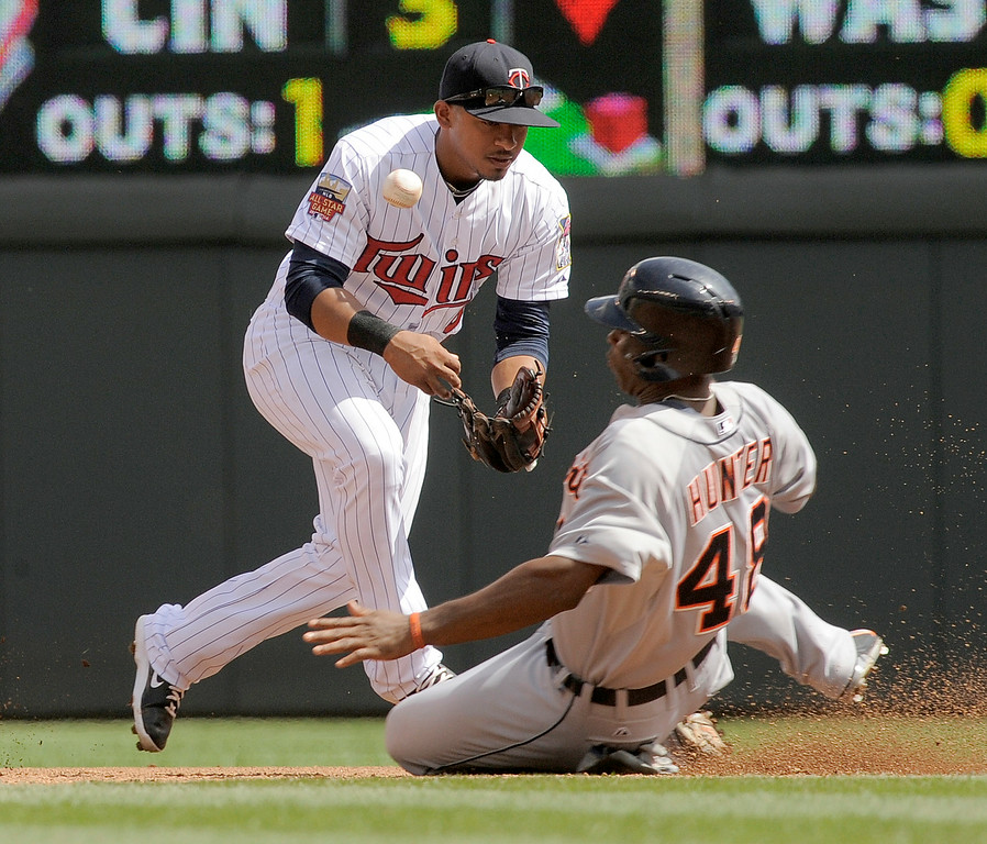 . Minnesota Twins shortstop Eduardo Escobar, left, mishandles the throw as Detroit Tigers� Torii Hunter, right, slides in safely on a fielder\'s choice during the third inning of a baseball game in Minneapolis, Sunday, Aug. 24, 2014. (AP Photo/Tom Olmscheid)
