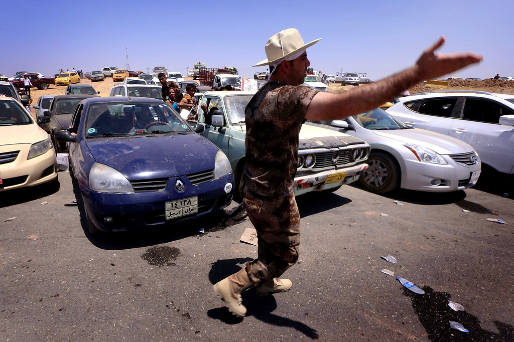 . An Iraqi Kurdish security guard gestures as families fleeing violence in Iraq\'s northern Nineveh province wait in their vehicles at a Kurdish checkpoint in Aski kalak, 40 kms West of Arbil, in the autonomous Kurdistan region, on June 10, 2014. Suspected jihadists seized Iraq\'s entire northern province of Nineveh and its capital Mosul, the country\'s second-largest city, in a major blow to authorities, who appear incapable of stopping militant advances. SAFIN HAMED/AFP/Getty Images