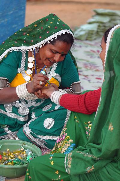 Ladies applying mehendi on their hands at Surajkund Mela. Suraj Kund Mela 2009 held in Haryana (outskirts of Delhi), North India. The Suraj Kund Mela is an annual fair held near Delhi. Folk dances, handicrafts and a lot of fun.