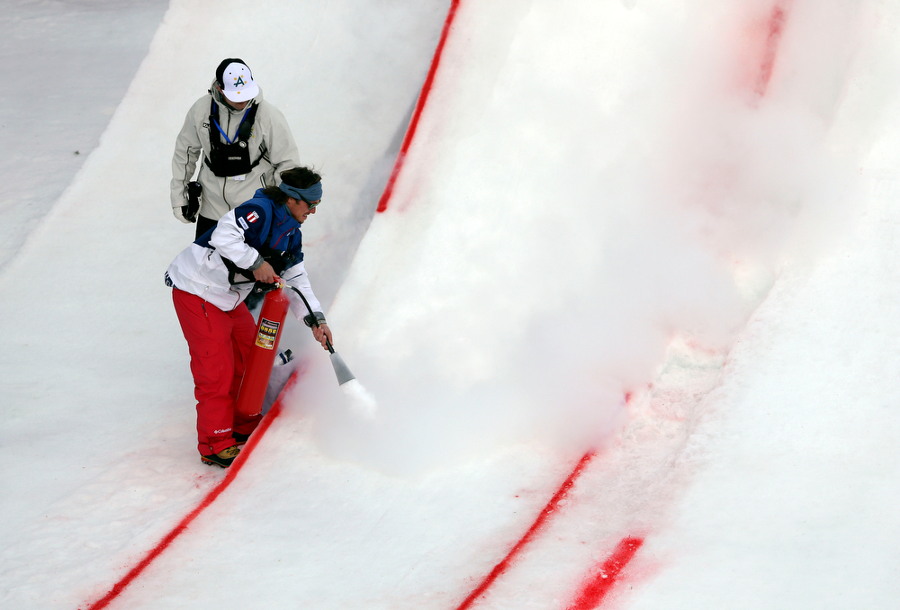 . Course workers prepare the surface of a jump before the start of the women\'s freestyle skiing aerials qualifying at the Rosa Khutor Extreme Park, at the 2014 Winter Olympics, Friday, Feb. 14, 2014, in Krasnaya Polyana, Russia. (AP Photo/Sergei Grits)