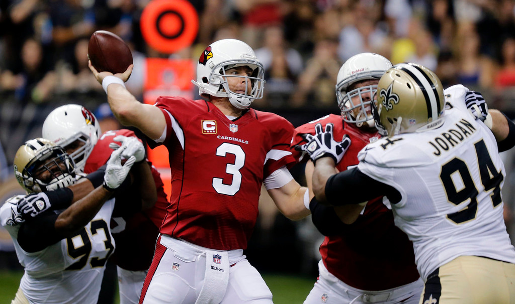 . Arizona Cardinals quarterback Carson Palmer (3) passes as New Orleans Saints defensive end Cameron Jordan (94) and outside linebacker Junior Galette (93) pressure him in the first half of an NFL football game in New Orleans, Sunday, Sept. 22, 2013. (AP Photo/Bill Haber)