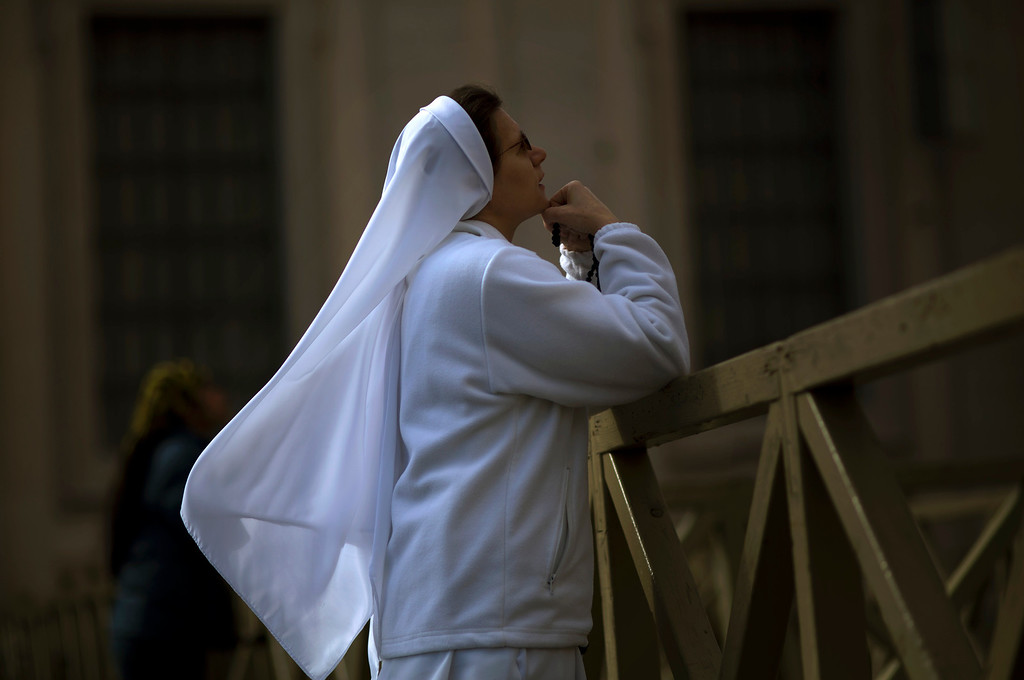 . A nun prays inside St. Peter\'s Square, at the Vatican, Tuesday, March 12, 2013. Cardinals enter the Sistine Chapel on Tuesday to elect the next pope amid more upheaval and uncertainty than the Catholic Church has seen in decades: (AP Photo/Emilio Morenatti)