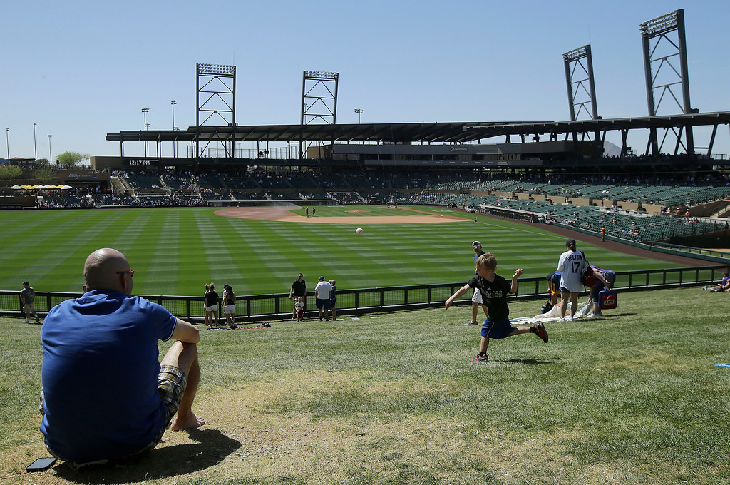 . Marty McGraw, left, watches as his son, Andrew, 4, throws a ball in the outfield lawn at Salt River Fields at Talking Stick before a spring training baseball game between the Colorado Rockies and the Milwaukee Brewers in Scottsdale, Ariz., Tuesday, March 22, 2016. (AP Photo/Jeff Chiu)