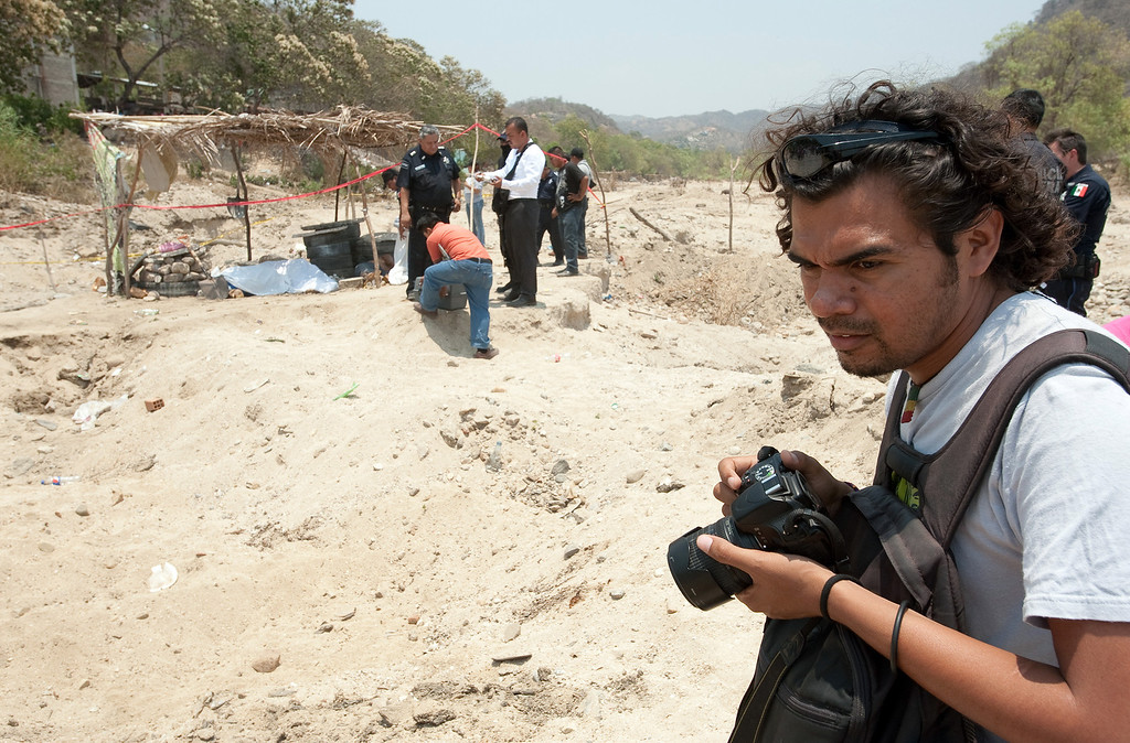 . Mexican journalists are under siege throughout the country both from organized crime and abusive government authorities. Reporters and photographers at El Sur newspaper in Acapulco take various precautions to deal with the threats they receive. Carlos Carbajal, a photographer at El Sur newspaper in Acapulco, covers a multiple homicide which claimed the lives of six men who were working loading sand and gravel into dump trucks in a dry riverbed in the community of Los Organos on the outskirts of Acapulco. (Keith Dannemiller/MCT)