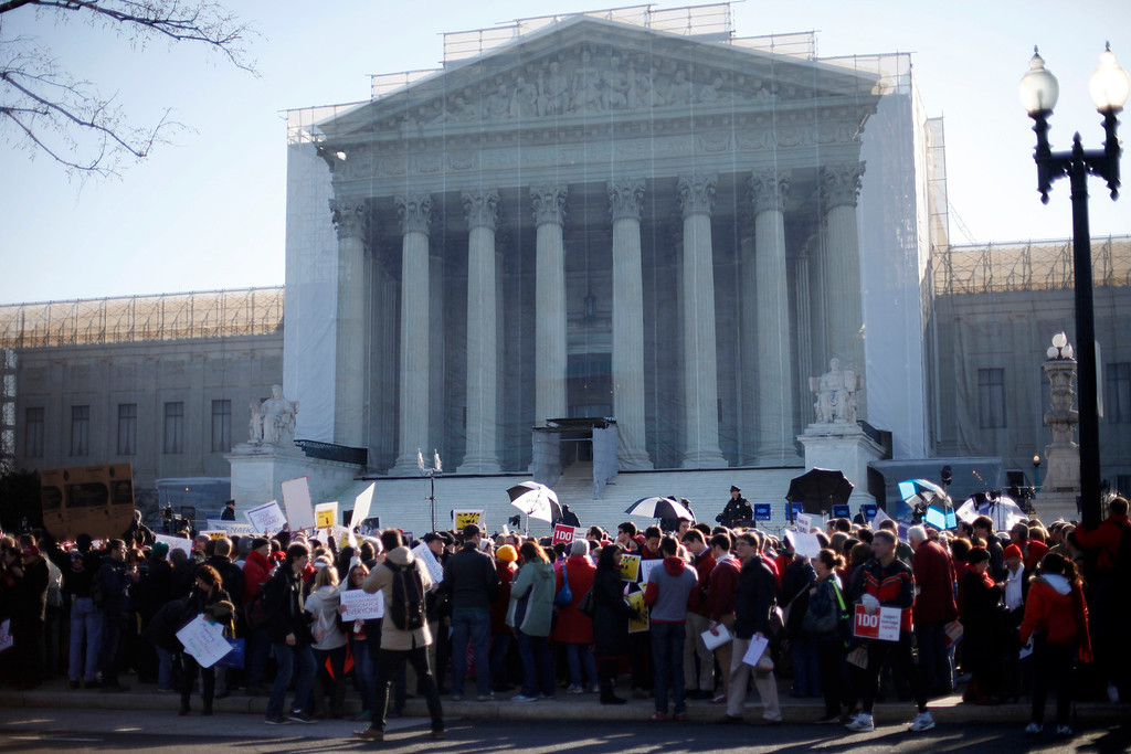 . Demonstrators stand outside the Supreme Court in Washington, Tuesday, March 26, 2013, where the court will hear arguments on California\'s voter approved ban on same-sex marriage, Proposition 8. (AP Photo/Pablo Martinez Monsivais)