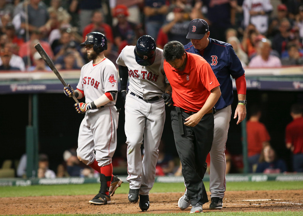. Boston Red Sox\'s Jackie Bradley Jr., center, is helped by a trainer after being hit by a pitch from Cleveland Indians\' Corey Kluber in the eighth inning during Game 2 of baseball\'s American League Division Series, Friday, Oct. 7, 2016, in Cleveland. (AP Photo/Aaron Josefczyk)