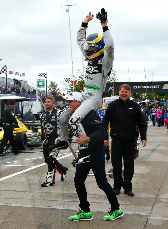 . Sebastien Bourdais celebrates on the shoulders of his father, Patrick, after winning the second race of the IndyCar Detroit Grand Prix auto racing doubleheader in Detroit, Sunday, May 31, 2015.  (AP Photo/Paul Sancya)
