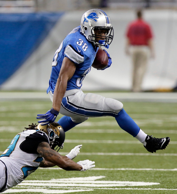 . Detroit Lions running back George Winn (38) jumps over Jacksonville Jaguars cornerback Jamell Fleming (29) in the second half of a preseason NFL football game at Ford Field in Detroit, Friday, Aug. 22, 2014.  (AP Photo/Duane Burleson)