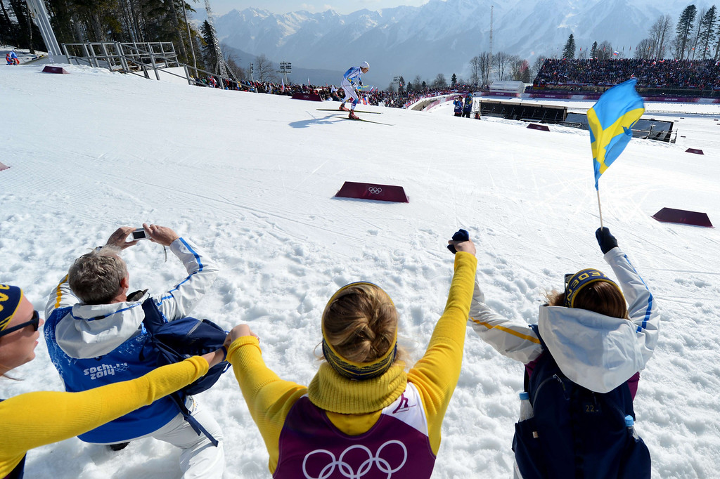 . Fans wave with Swedish flag as Sweden\'s Marcus Hellner competes in the Men\'s Cross-Country Skiing 4 x 10km Relay at the Laura Cross-Country Ski and Biathlon Center during the Sochi Winter Olympics on February 16, 2014 in Rosa Khutor near Sochi. KIRILL KUDRYAVTSEV/AFP/Getty Images