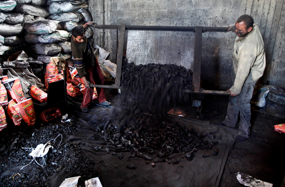. Palestinian workers sort coal to be sacked and sold, in the Jabalya refugee camp in the north of Gaza Strip on March 24, 2013. In adapting to years of border blockades and shortages, Gazans have become experts at recycling and making new out of old including turning scrap wood into charcoal to be used for barbecue grills and water pipes in local restaurants and coffee houses. (AP Photo/Hatem Moussa)
