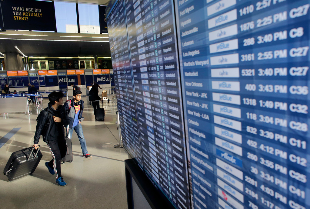 . Travelers walk past an airline reader board Tuesday, Nov. 22, 2016, at Logan International Airport, in Boston. Almost 49 million people are expected to travel 50 miles or more for the holiday, the most since 2007, according to AAA.  (AP Photo/Steven Senne)