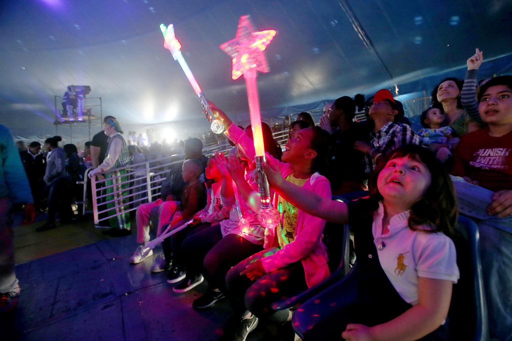 . Ila Sabonichi, 3, right, and Dionne Shepard, 7, center, both of Palo Alto, watch the UniverSoul Circus perform under the big top on Hegenberger Road in Oakland, Calif., on Friday, April 5, 2013.  (Jane Tyska/Staff)