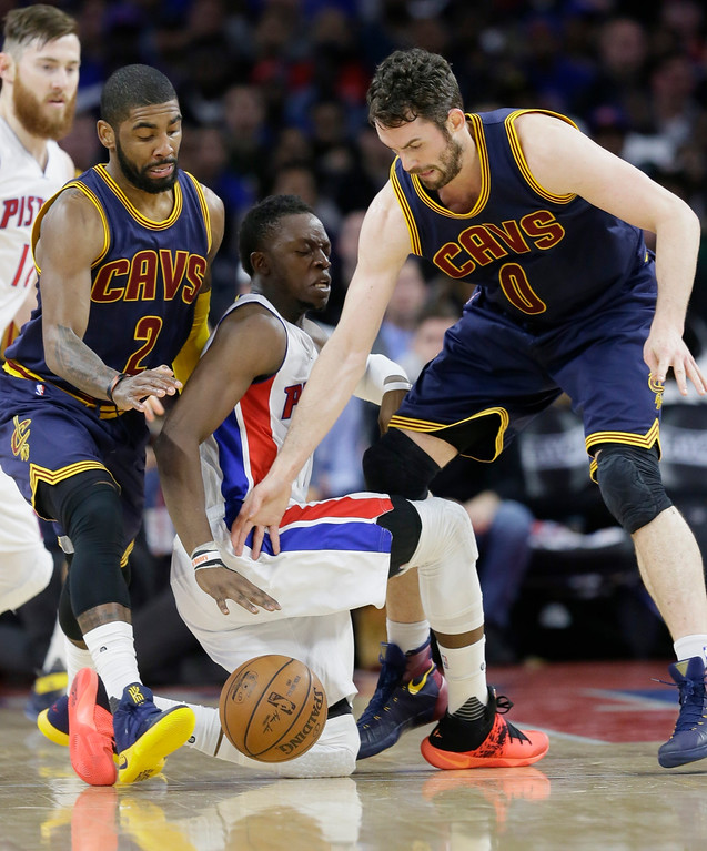 . Cleveland Cavaliers guard Kyrie Irving (2) and forward Kevin Love (0) reach in as Detroit Pistons guard Reggie Jackson (1) looses control of the ball during the first half in Game 4 of a first-round NBA basketball playoff series, Sunday, April 24, 2016 in Auburn Hills, Mich. (AP Photo/Carlos Osorio)