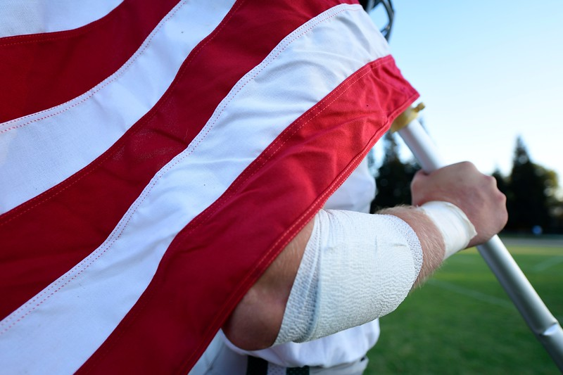 De La Salle's Jon Puckett (50) holds the U.S. flag before the start of their game at Central Catholic High School in Modesto, Calif. on Friday, Aug. 30, 2019. (Jose Carlos Fajardo/Bay Area News Group)