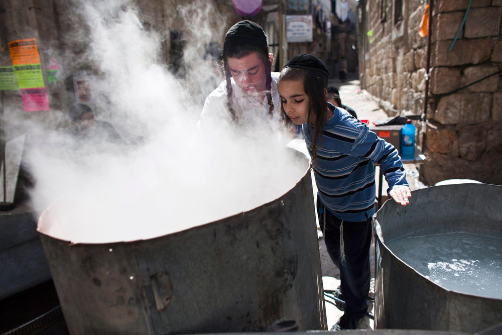 . An ultra-Orthodox Jewish boy looks inside a pot containing boiling water where cooking utensils are dipped to remove remains of leaven in preparation for the Jewish holiday of Passover, in Jerusalem\'s Mea Shearim neighborhood March 24, 2013. Passover, which starts at sundown Monday, commemorates the flight of Jews from ancient Egypt, as described in the Exodus chapter of the Bible. According to the account, the Jews did not have time to prepare leavened bread before fleeing to the promised land. REUTERS/Nir Elias