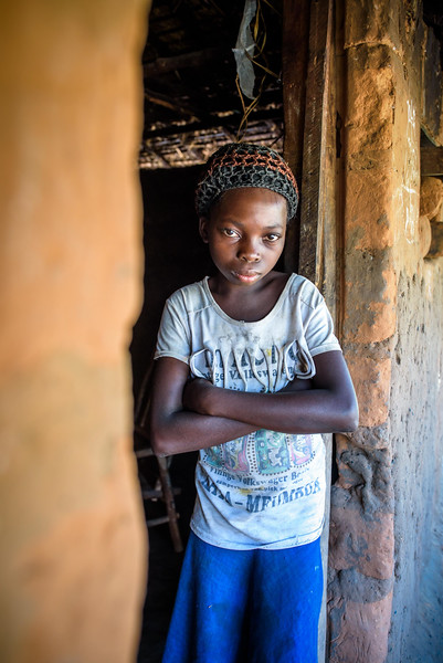 """Portrait of Marie Ngalula, 14 yr-old girl.  Marie lives with her father, Alexandre Tshimanga, her mother, Ntumba Kalombo Antoinette and her brothers and sisters: 1-Kena Tshimanga, 12 2-Kankonde Moise, 10 3-Munamba Angel, 8 4-Musungayi Andre, 6 5-Mubuyi Tshimanga, 4  Marie lives in a small village outside of Kananga, Democratic Republic of Congo, DRC, called Tubuluku, which means antelopes (plural). Her house is a two-room hut with a thatched roof.  Handful of wooden chairs are the only furniture. She lives here with an extended family of 13.  Home Life Marie is a bright girl but there is a sadness in her eyes. Marie's mother is in the nearby health clinic with a staph infection that has caused a huge abscess on her right side. It has become very serious. As a result, Marie has assumed many of the household duties.  She's forced, at 14, to assume the duties of an adult. Besides cooking for her brothers and sisters, she sweeps up the husks from palm nuts she crushes. She saves the husks to use as kindling for the fire. Marie and her siblings all sleep together in one room, huddled together for warmth and cover by an old and torn mosquito net.  School Marie's father laments his inability to send her back to school. """"Marie is intelligent,"""" he says. """"She could help me very much someday.  I'd like to send her back to school but I can't afford it. I'd like if she could further her studies even as far as university so that she can help me take care of her brothers and sisters someday.""""  Marie and her friends often play on the grass in front of the school they can't afford to go to.  Hunger Marie's family is desperately hungry in the days we visit them. Because her mother is sick and his father spends his days tending to her in the clinic, there is no money for food. Because there isn't any cassava flour and cornmeal to make fufu, a bread-like dish that's a Congolese staple, Marie and her siblings pick potato leaves from the garden. Marie sharpens a knife on a rock and uses """