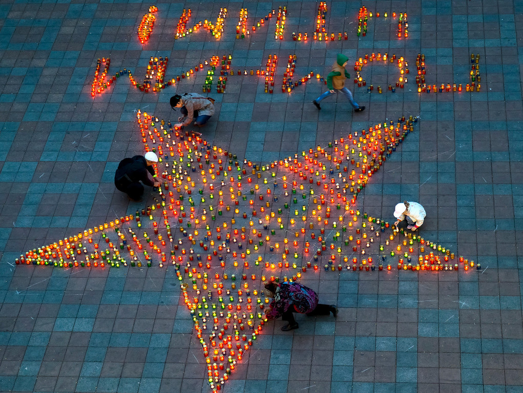 """. People light candles set in the shape of a star during Victory Day celebrations in Odessa, Ukraine, Friday, May 9, 2014. In the Black Sea port of Odessa, which last week was rocked by violent clashes between pro-Russian forces and supporters of the central government that left nearly 50 people dead, the local governor issued an order banning public display of Russian flags. Writing reads \""""We remember, we respect\"""". (AP Photo/Vadim Ghirda)"""