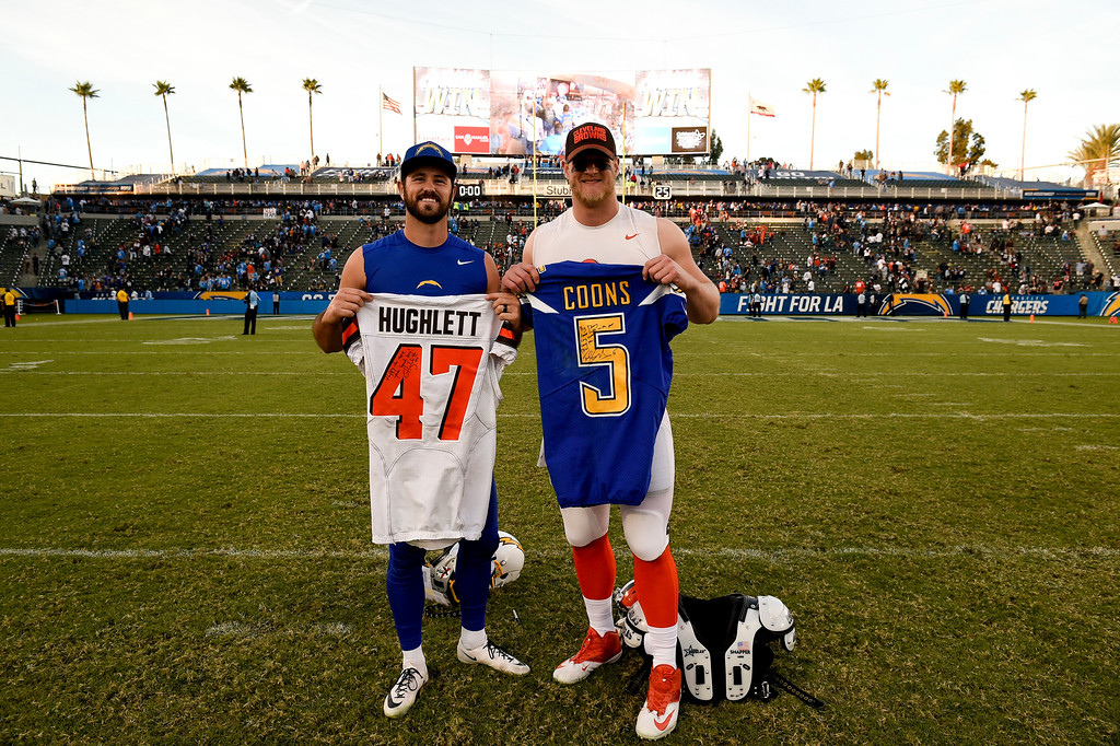 . Los Angeles Chargers kicker Travis Coons, left, and Cleveland Browns long snapper Charley Hughlett exchange jerseys after an NFL football game Sunday, Dec. 3, 2017, in Carson, Calif. (AP Photo/Kelvin Kuo)