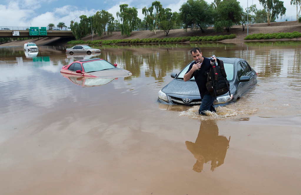 . Jim Sampson retrieves items from his 2002 Toyota Corolla stuck in flood waters on I-10 east at 43rd Ave. after monsoon rains flooded the freeway in Phoenix, Monday, Sept. 8, 2014. Heavy storms pounded the Phoenix area early Monday, flooding major freeways, prompting several water rescues and setting an all-time single-day record for rainfall in the desert city. (AP Photo/The Arizona Republic, Michael Chow)