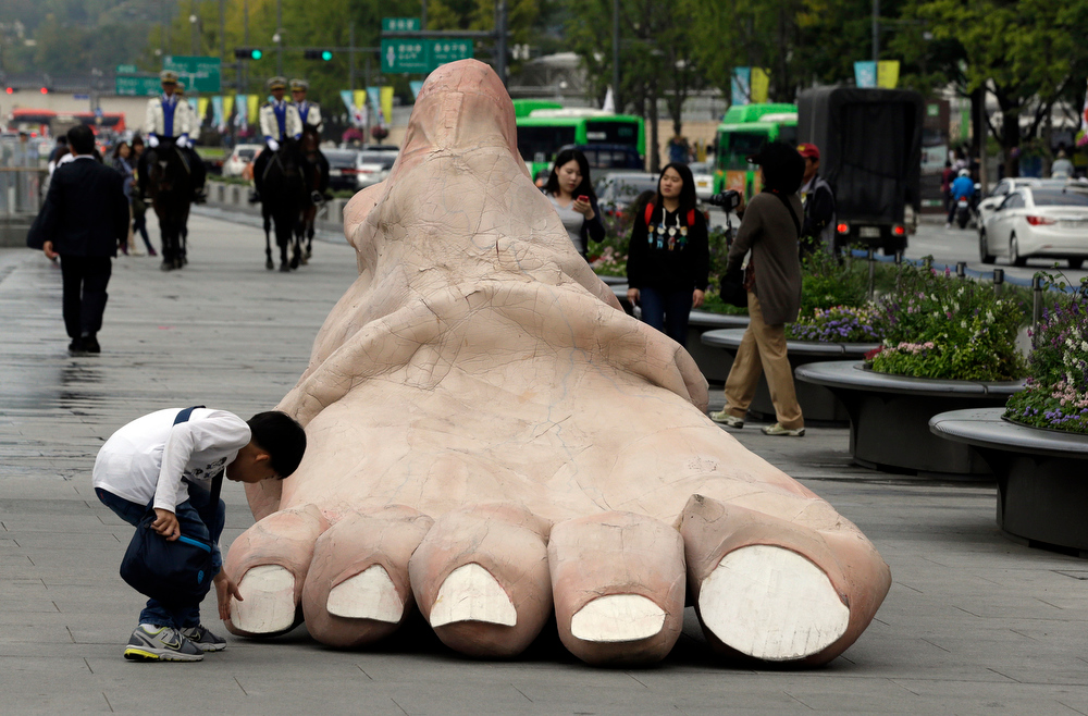 Description of . A boy touches a massive foot during the Human Body Parts performance on the street in Seoul, South Korea, Thursday, Oct. 4, 2012. The performance is part of the Hi Seoul Festival which runs from Oct. 1 through Oct. 7. (AP Photo/Lee Jin-man)