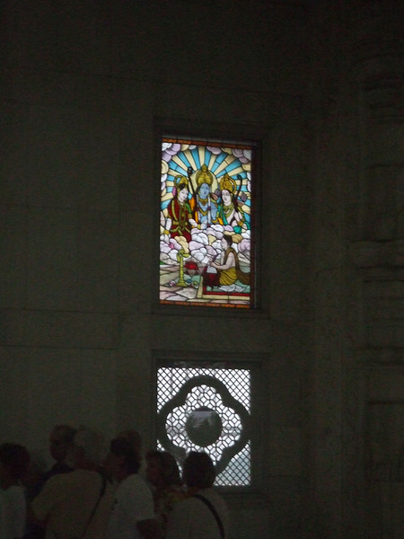 All devotees welcome. Stained glass portraying Hindu gods with Buddha