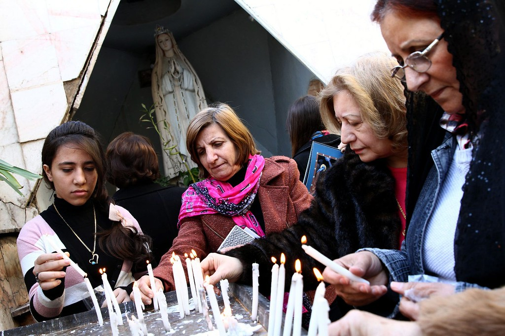 . Iraqi Christians light candles as they celebrate the Christmas at the Virgin Mary Chaldean Christian church in Baghdad, Iraq, 25 December 2013. Christians comprise about 3 percent of the population in Iraq.  EPA/ALI ABBAS