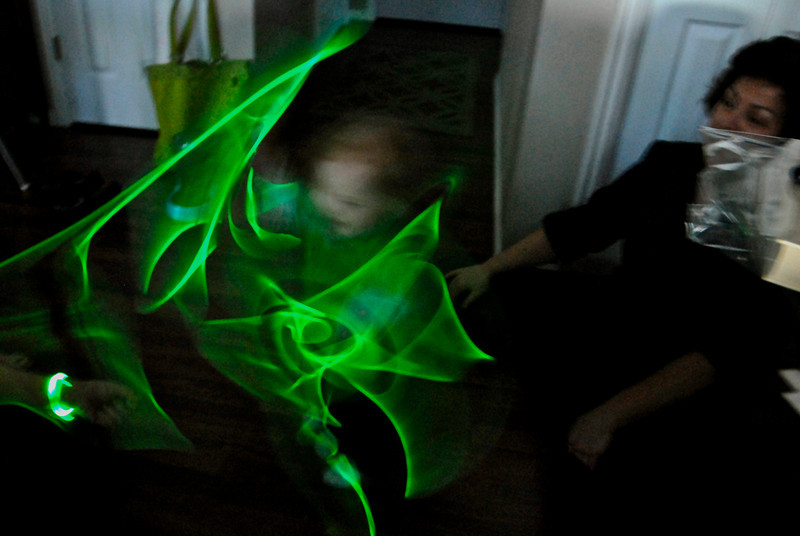 2011/3/17 – HAPPY ST. PATRICK'S DAY! This is how Olin celebrated. He had several glow stick that he swung all around in the near darkness while I tried to get a long exposure..I took a ton and this worked best because you can see Olin and Lisa and we got a cool pattern with the swirling glow sticks.