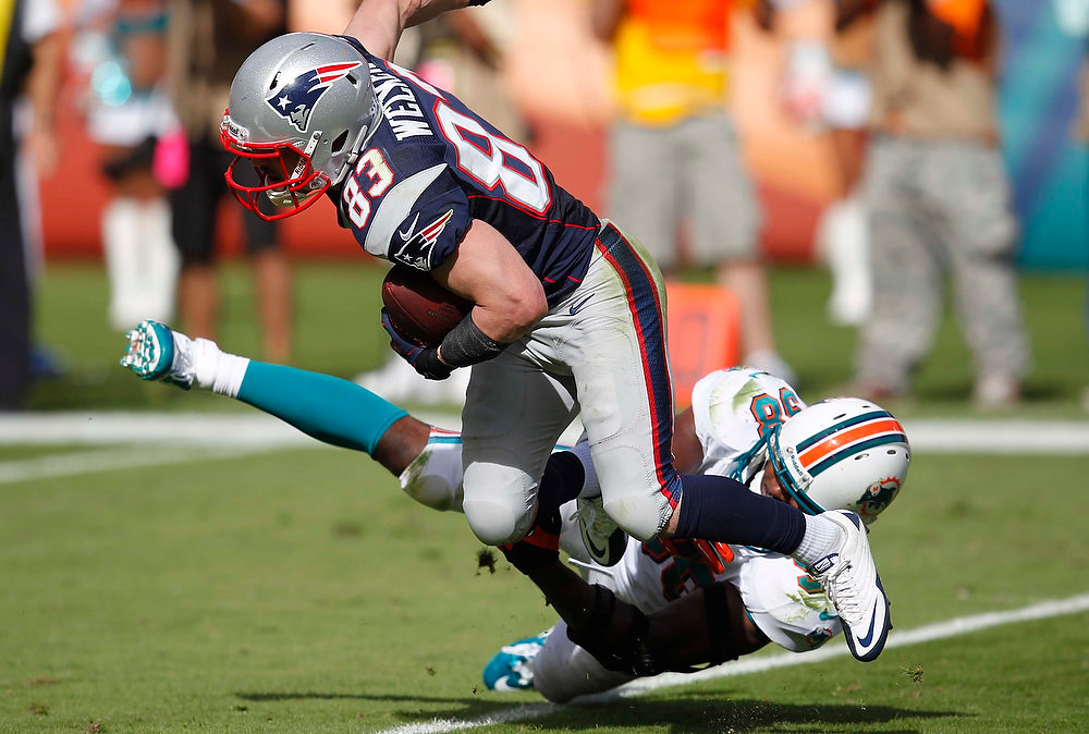Description of . Miami Dolphins middle linebacker Karlos Dansby (58) attempts to tackle New England Patriots wide receiver Wes Welker (83) during the first half of an NFL football game, Sunday, Dec. 2, 2012, in Miami. (AP Photo/Wilfredo Lee)