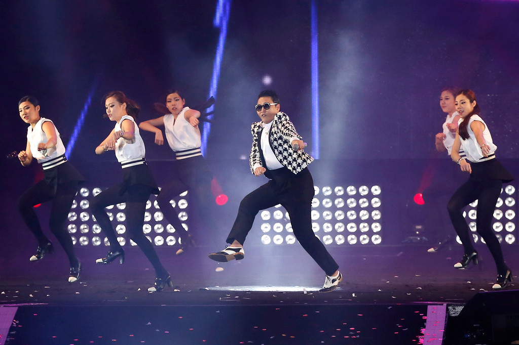 """. South Korean rapper PSY, in a checkered jacket, performs his new song \""""Gentleman\"""" in his concert titled \""""Happening\"""" in Seoul, South Korea Saturday, April 13, 2013. PSY\'s first new single since his megahit \""""Gangnam Style\"""" was released in 119 countries on Friday, his agency said. (AP Photo/Kin Cheung)"""