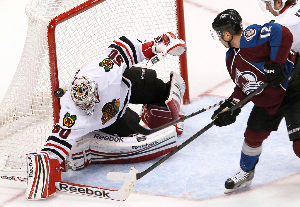 . Chicago Blackhawks goalie Corey Crawford (L) has the puck bounce off the pipe on a shot on goal by Colorado Avalanche\'s Chuck Kobasew (R) in their NHL hockey game in Denver March 8, 2013. REUTERS/Rick Wilking