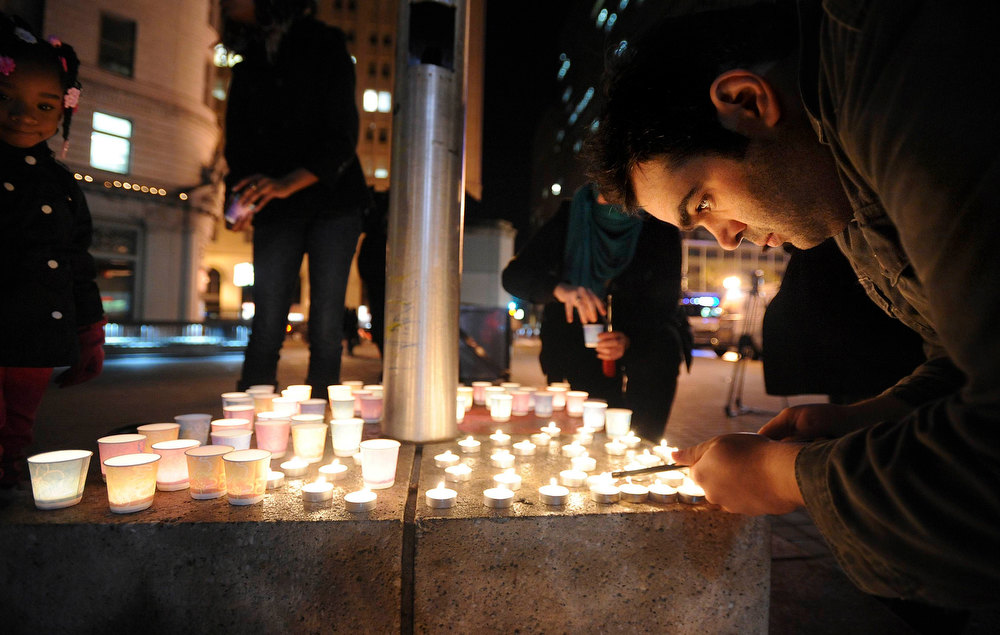 . Mario Buda lights candles during a vigil commemorating victims of a Connecticut elementary school shooting in Oakland, California, December 14, 2012. Twenty schoolchildren were slaughtered by a heavily armed gunman who opened fire at a suburban elementary school in Connecticut on Friday, ultimately killing at least 27 people including himself in the one of the worst mass shootings in U.S. History. The 20-year-old gunman, identified by law enforcement sources as Adam Lanza, fired what witnesses described as dozens of shots at Sandy Hook Elementary School in Newtown, Connecticut, which serves children from ages 5 to 10. REUTERS/Noah Berger