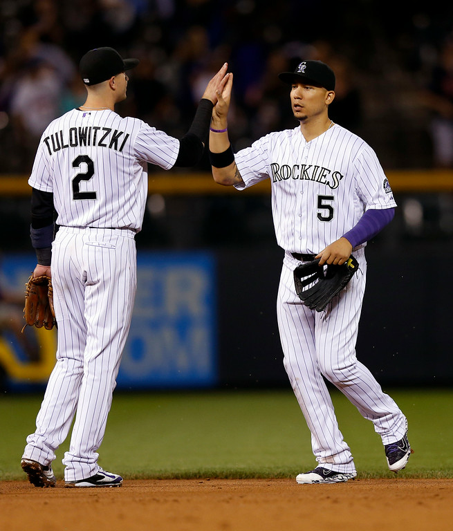 . Colorado Rockies\' Carlos Gonzalez (5) and Troy Tulowitzki (2) celebrate the Rockies\' 6-2 victory over the Minnesota Twins in a baseball game Friday, July 11, 2014, in Denver. (AP Photo/Jack Dempsey)