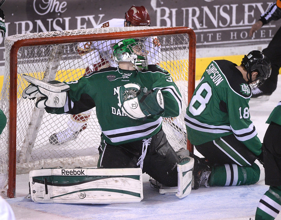 . DENVER, CO. - JANUARY 24:  Denver left wing Trevor Moore (8) snuck the puck into the net behind North Dakota goalie Clarke Saunders late in the third period. The University of Denver hockey team hosted North Dakota at Magness Arena Friday night, January 24, 2014. Photo By Karl Gehring/The Denver Post