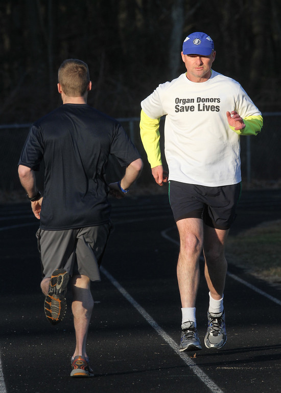 . Donald Davis, 54, of Reading, right, will run the Boston Marathon route Sunday a week early to raise money for DonateLife and promote organ and tissue donation. His nephew Bryon Patten, 34, of Woburn, left, will run with him forwards to keep him on course. Both are originally from Billerica. They are doing a run at the Marshall Middle School track to work on their pace. (SUN/Julia Malakie)