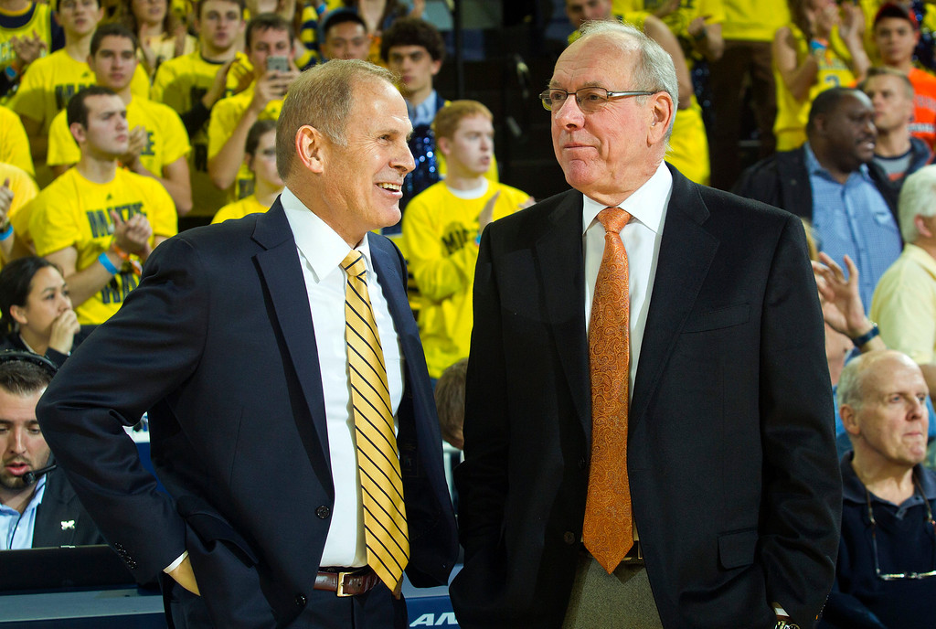 . Michigan head coach John Beilein, left, and Syracuse head coach Jim Boeheim, right, talk on the court before the first half of an NCAA college basketball game at Crisler Center in Ann Arbor, Mich., Tuesday, Dec. 2, 2014. (AP Photo/Tony Ding)