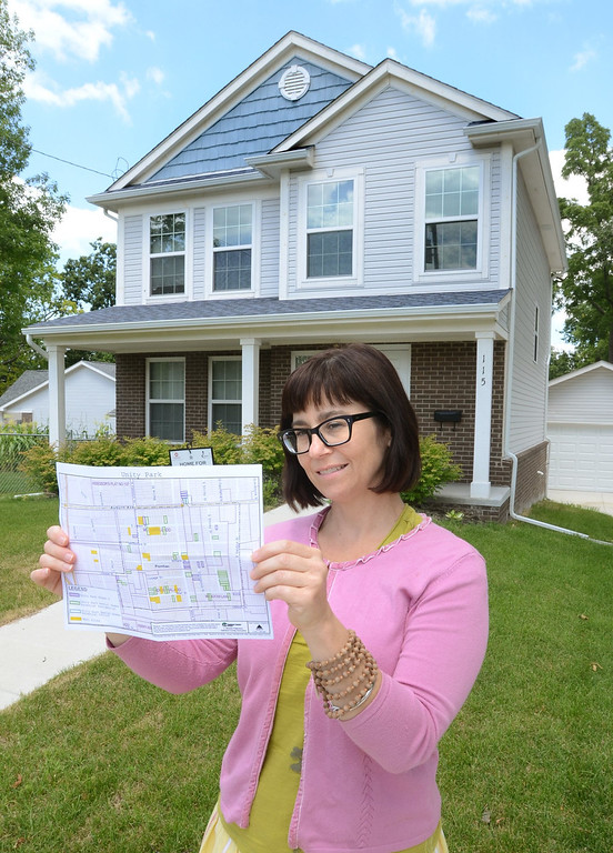 . Kristen Elliott, vice president of Development for the Community Housing Network, with a site plan, in front of the type of house that will be built for a 32-unit rental home development in Unity Park in Pontiac.  Thursday, July 25, 2013.  The Oakland Press/TIM THOMPSON